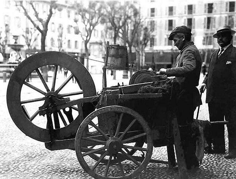 """Inizio secolo XX, arrotino (detto in milanese """"moleta"""" in piazza Fontana (Milano), con il suo carretto"""