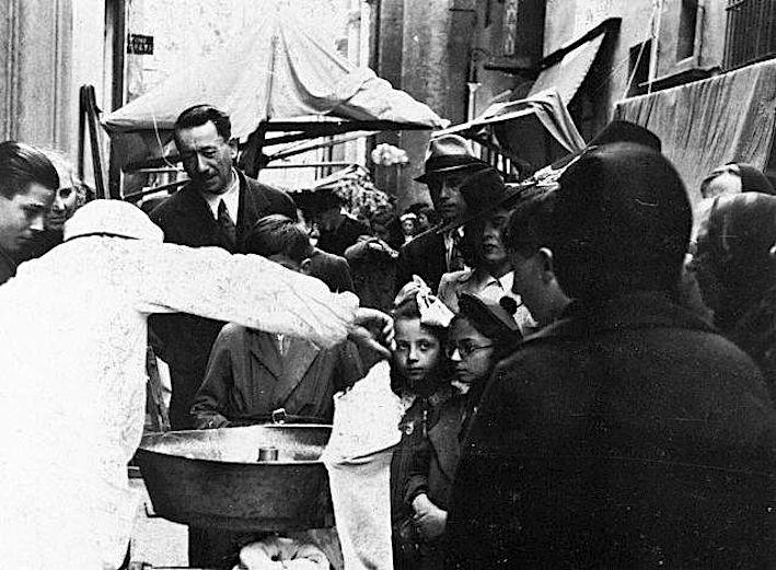 venditore-di-zucchero-filato-durante-una-fiera-in-via-Altabella-negli-anni-Trenta.-Foto-N.-Comaschi